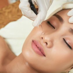 Close-up shot of attractive young woman lying on treatment table with closed eyes while unrecognizable beautician using high frequency infrared spot remover on her facial skin