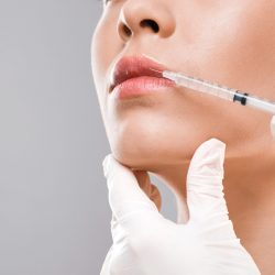 Closeup of nurse making lip injection for unrecognizable young woman, copy space